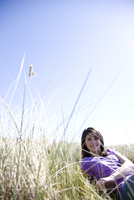 Young woman lying down on a field smiling 20025324697| 写真素材・ストックフォト・画像・イラスト素材|アマナイメージズ