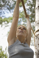 Young woman at obstacle course hanging from a rope 20025324956| 写真素材・ストックフォト・画像・イラスト素材|アマナイメージズ