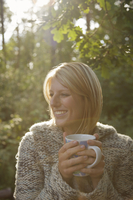 Smiling young woman in a forest holding a mug looking to one side
