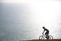 Man cycling by the ocean 20025325055| 写真素材・ストックフォト・画像・イラスト素材|アマナイメージズ