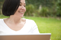 Close up of a smiling woman using a laptop computer