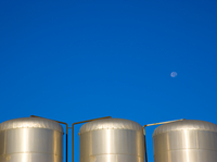 Metal storage tanks against a cloudeless blue sky with moon