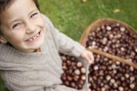 Smiling young boy holding chestnuts 20025325295| 写真素材・ストックフォト・画像・イラスト素材|アマナイメージズ