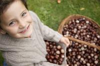 Smiling young boy holding chestnuts 20025325296| 写真素材・ストックフォト・画像・イラスト素材|アマナイメージズ