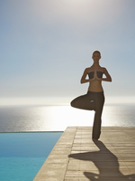 Young woman practicing yoga by a swimming pool with ocean in the background 20025325365| 写真素材・ストックフォト・画像・イラスト素材|アマナイメージズ