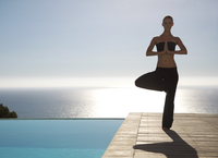 Young woman practicing yoga by a swimming pool with ocean in the background