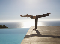 Young woman practicing yoga by a swimming pool with ocean in the background 20025325367| 写真素材・ストックフォト・画像・イラスト素材|アマナイメージズ
