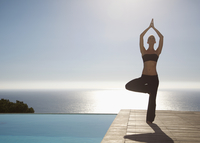 Young woman practicing yoga by a swimming pool with ocean in the background 20025325369| 写真素材・ストックフォト・画像・イラスト素材|アマナイメージズ