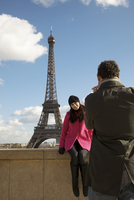 Back view of a man taking a photo of a woman in front of the Eiffel Tower 20025325383| 写真素材・ストックフォト・画像・イラスト素材|アマナイメージズ