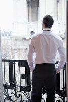 Back view of businessman standing on the balcony of a Parisian hotel