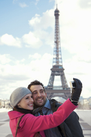 Couple taking a photo of themselves in front of the Eiffel Tower 20025325388| 写真素材・ストックフォト・画像・イラスト素材|アマナイメージズ