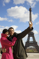 Couple taking a photo of themselves in front of the Eiffel Tower