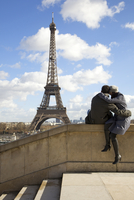 Back view of a couple sitting on a wall in front of the Eiffel Tower 20025325390| 写真素材・ストックフォト・画像・イラスト素材|アマナイメージズ