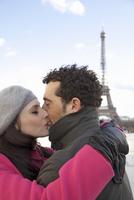 Couple kissing in front of the Eiffel Tower 20025325400| 写真素材・ストックフォト・画像・イラスト素材|アマナイメージズ