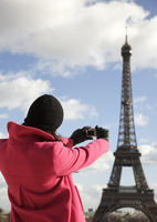 Back view of a woman taking a photo of the Eiffel Tower