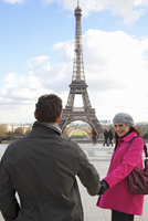 Couple holding hands in front of the Eiffel Tower 20025325405| 写真素材・ストックフォト・画像・イラスト素材|アマナイメージズ