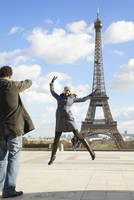 Back view of a man taking a photo of a woman in front of the Eiffel Tower 20025325408| 写真素材・ストックフォト・画像・イラスト素材|アマナイメージズ