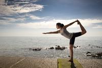Woman practicing yoga by the ocean 20025325410| 写真素材・ストックフォト・画像・イラスト素材|アマナイメージズ