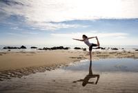 Woman practicing yoga on a beach 20025325426| 写真素材・ストックフォト・画像・イラスト素材|アマナイメージズ