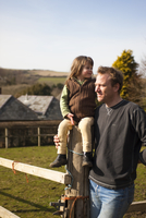 Man holding girl sitting on a paddock fence