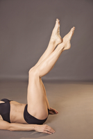 Woman lying on her back with legs raised wearing black underwear, headless
