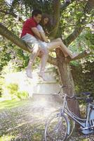 Young Couple Sitting on Tree Branch Hugging 20025325613| 写真素材・ストックフォト・画像・イラスト素材|アマナイメージズ
