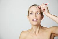 Woman Holding Pencil against Forehead 20025325673  写真素材・ストックフォト・画像・イラスト素材 アマナイメージズ