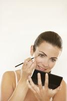 Woman Holding Handheld Mirror Applying Eyeshadow