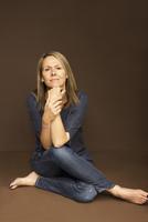 Woman Sitting Cross Legged Leaning on Elbows