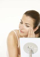 Woman Looking into the Mirror Applying Eye Cream
