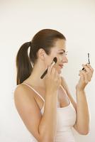 Woman Holding Compact Applying Blush