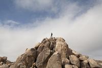 Man Admiring View On Top Of Rock Formation 20025325888| 写真素材・ストックフォト・画像・イラスト素材|アマナイメージズ