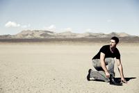 Man Crouching in Desert Landscape 20025325912| 写真素材・ストックフォト・画像・イラスト素材|アマナイメージズ