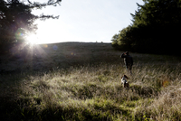 Man and Dog Walking Uphill on Field