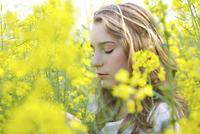 Profile of Young Woman amongst Canola Flowers 20025326085| 写真素材・ストックフォト・画像・イラスト素材|アマナイメージズ