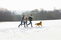 Teenage Girls and Dog Running in Snow 20025326092| 写真素材・ストックフォト・画像・イラスト素材|アマナイメージズ