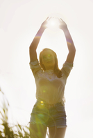 Young Woman Standing in a Field with Sun Shining through her Hands 20025326106| 写真素材・ストックフォト・画像・イラスト素材|アマナイメージズ