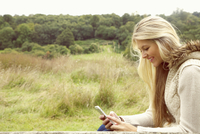 Young Woman in Field Using Smartphone