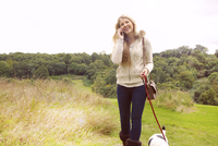 Young Woman Walking Dog and Using Phone