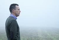 Man Standing in Field 20025326323| 写真素材・ストックフォト・画像・イラスト素材|アマナイメージズ