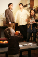 View of a small girl holding an orange.