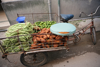 View of a tricycle cart filled with vegetables.