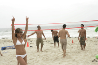 A group of people are playing volleyball on a beach.