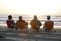 View of four people relaxing by the sea. 20025326438| 写真素材・ストックフォト・画像・イラスト素材|アマナイメージズ