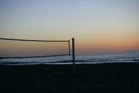 A net is tied on poles on a beach in the evening.