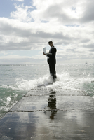 View of a man standing near a sea with his laptop.