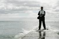 View of a man with a laptop near the sea.