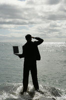View of a man standing in the sea with his laptop.