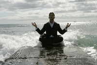 View of a man doing meditation near the sea.
