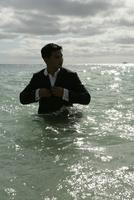View of a man standing in the sea. 20025326479| 写真素材・ストックフォト・画像・イラスト素材|アマナイメージズ